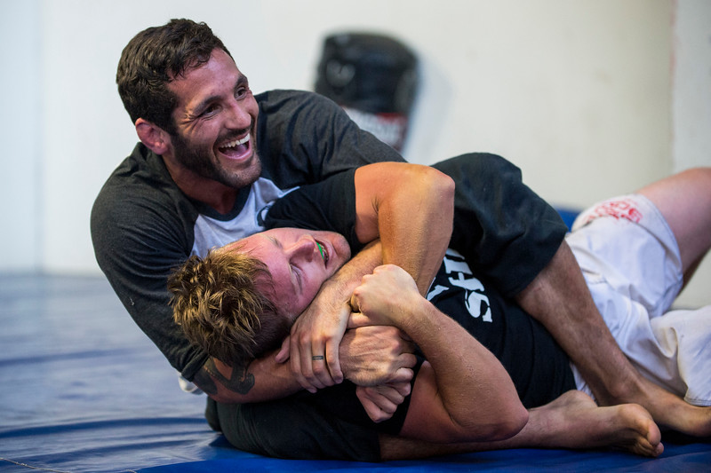 Lucus Montoya (top) is all smiles as he works on his grappling skills with Colten Bybee (bottom) at Foley's Mixed Martial Arts Gym in Ogden on July 14, 2016. Montoya broke his arm during a fight and has been struggling to get consistently back in the ring after three surgeries to repair his ulna.