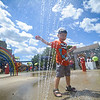 6/17/16 LEOMINSTER with story--Michael Goranson, 4, of Leominster swats at the water jet during Fridays grand re-opening of the Louis Charpentier Park in Leominster.   Sentinel & Enterprise photo/Jeff Porter