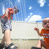 6/17/16 LEOMINSTER with story--Michael Goranson, 4, of Leominster (left) plugs the water jet next to 7 month old Max Antonio Riviera of Leominster during Fridays grand re-opening of the Louis Charpentier Park in Leominster.   Sentinel & Enterprise photo/Jeff Porter