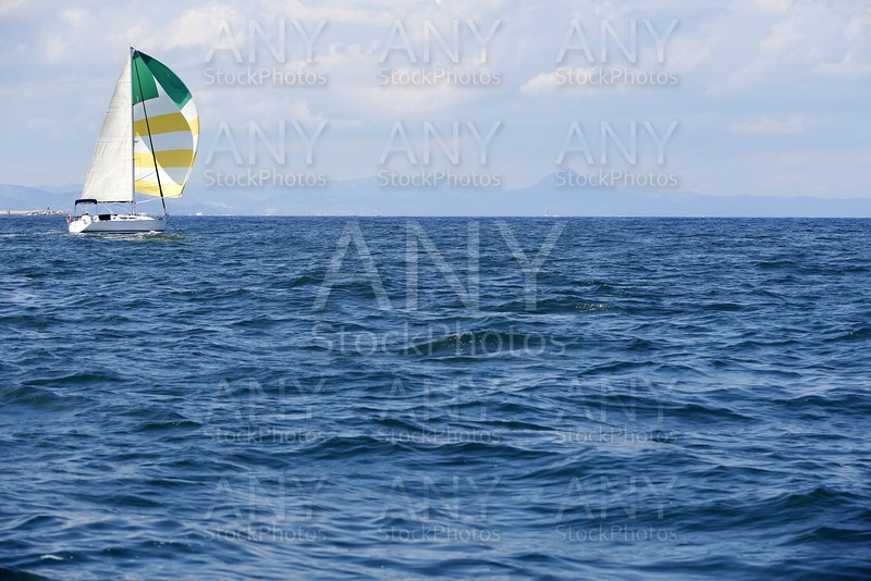 Blue sea with sailboat sailing the ocean surface