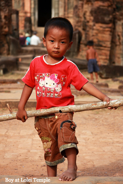 little boy playing with a long piece of branch at Lolie Temple, Angkor Wat