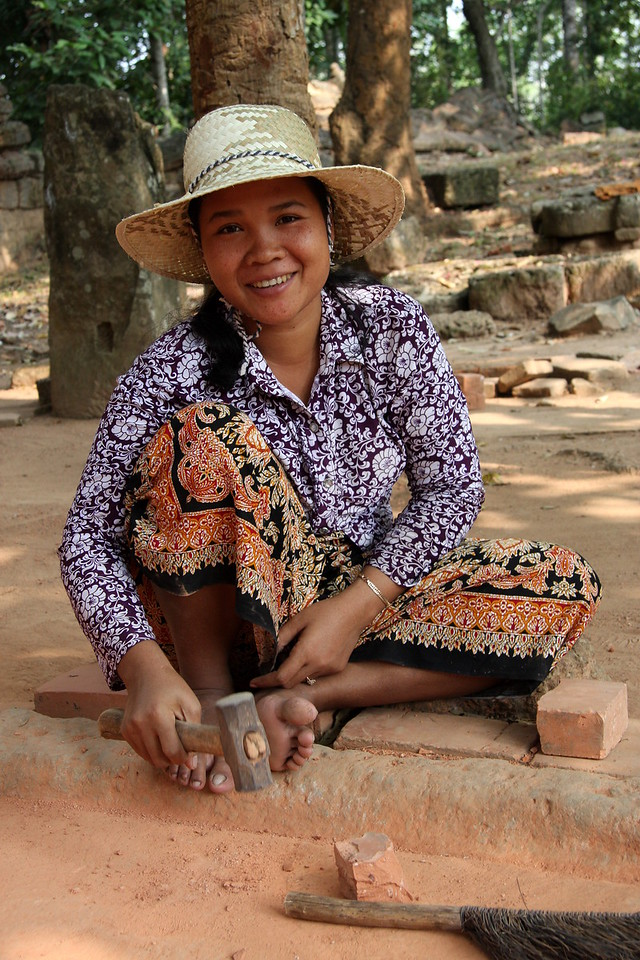breaking up bricks into fine powder for use in repairs at Lolie Temple, Angkor Wat