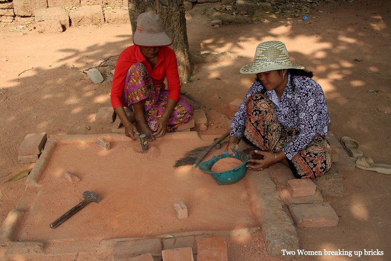 two ladies breaking up bricks into fine powder for use in repairs at Lolie Temple, Angkor Wat