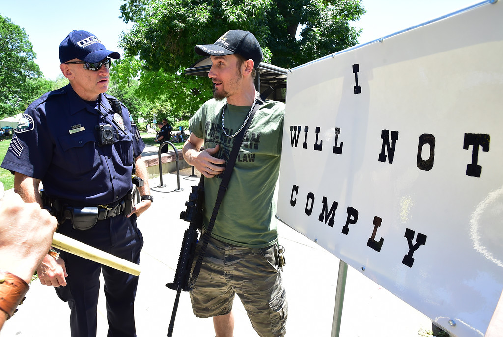 . Sgt A. McNiven checks with with Bacca, who asked that his first name not be used, during a Second Amendment rally in Boulder on Saturday. Boulder Police Department officers checked in with Bacca, who was carrying an AR-15, to make sure he understood the regulations about open carry. They also asked him to remove his magazine from his rifle. He politely refused to do that.  For more photos and video go to dailycamera.com. Paul Aiken Staff Photographer