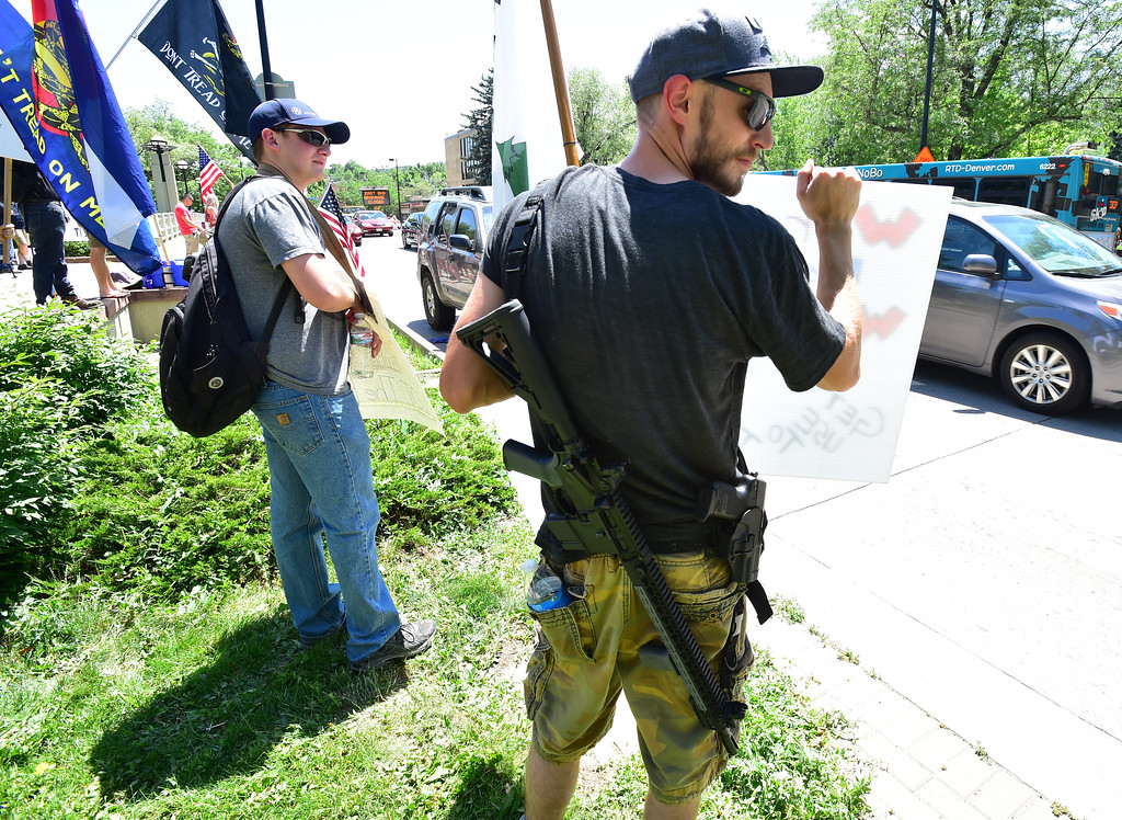 . Ryan, who only gave his first name, and John Smith, right, protest along Broadway during a Second Amendment rally in Boulder on Saturday.  For more photos and video go to dailycamera.com. Paul Aiken Staff Photographer