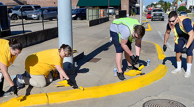 KEVIN HARVISON   Staff photo Volunteers work togather on Carl Albert Parkway. Volunteers painted curbs and fire hydrants from Main Street to Sixth Street on Choctaw Avenue and West Street to Tandy Town on Carl Albert Parkway along with portions of Washington Avenue.