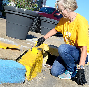 KEVIN HARVISON   Staff photo Cheryl McElhany with the Pittsburg County Health Department paints a curb during the combined City of McAlester and Pittsburg County Heath Department Volunteer Day in conjunction with Pride in McAlester.