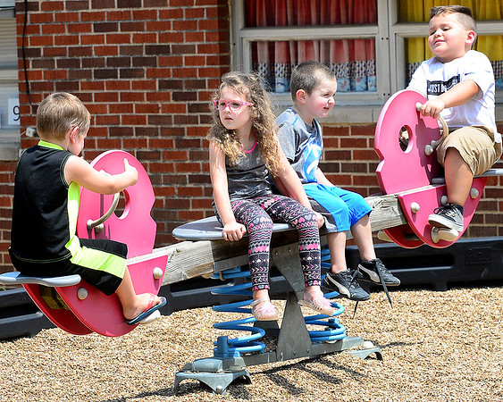 KEVIN HARVISON | Staff photo<br /> Cassandra Fletcher and Bentley Davis rest on the center of the teeter totter at Jefferson Early Childhood Center.