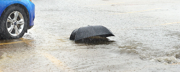 KEVIN HARVISON | Staff photo<br /> An umbrella gets swept away in a local parking lot Friday.