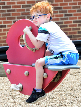 KEVIN HARVISON | Staff photo<br /> Leeam Barrett hangs on while playing on a Jefferson Early Childhood Center playground teeter totter.