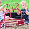 "KEVIN HARVISON | Staff photo<br /> Tilley McCann, right, waits for permission before fixing the ""flat"" tire on a Jefferson Early Childhood Center playground car during recess."