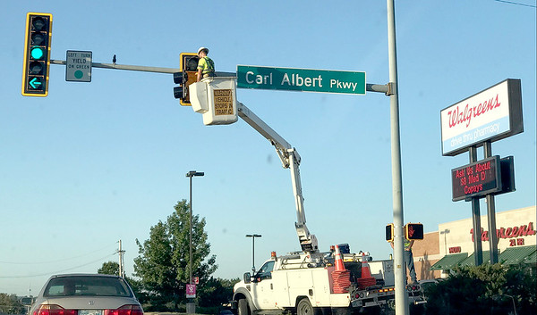 ADRIAN O'HANLON lll | Staff photo<br /> A crew member fixes a light at the intersection of Carl Albert Parkway and Strong Boulevard on Wednesday morning.