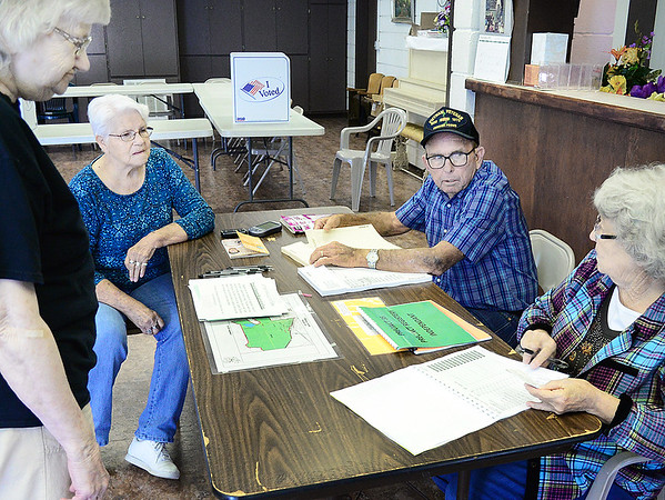 Kevin Harvison | Staff photo<br /> Pictured from left, an unidentified Hartshorne voter is helped by Pricinct 35 Election Board workers Alice Gragg, inspector, Robert Ray, clerk and Minne Lynn Scott, judge Tuesday during the Hartshorne city election.