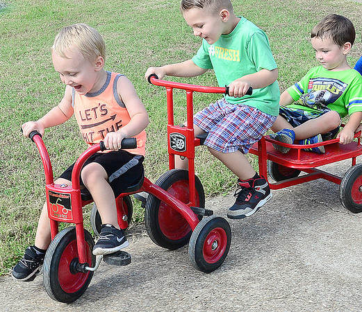 Kevin Harvison | Staff photo<br /> The race is on at Washington Early Childhood Center. Pictured from left Christian Tarullo, Kabin Cooper and Eli Free enjoy a friendly race as the WECC sidewalk double as a race track.