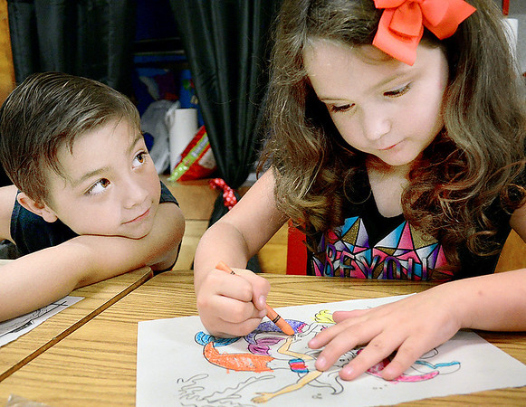 Kevin Harvison | Staff photo<br /> McAlester students Gavan Auten, left, waits on his classmate Aiyannah Young, right, to finish her coloring project before moving on to the tables next project.