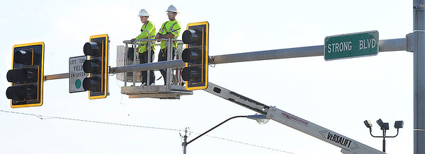 Kevin Harvison | Staff photo<br /> A crew exmines the new light at the intersectiuon of Carl Albert Parkway and Stroung Boulevard.