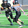 Kevin Harvison | Staff photo<br /> A McAlester third grade running back splits the Coweta defenders during a home game at Jeff Lee Stadium Saturday.