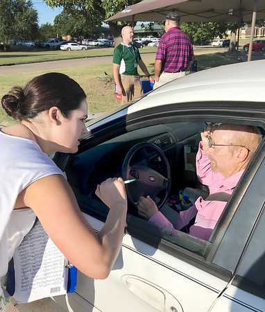 KEVIN HARVISON | Staff photo<br /> McAlester Regional Health Center Marketing Coordinator Ashley Kennon visits with Timmothy Ramsey after he signed a petition for State Questoin 820 petition, on her day off from hospital duties.