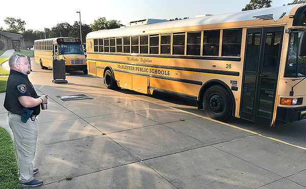 KEVIN HARVISON | Staff photo<br /> McAlester Police Officer Jeremy Busby watches as buses unload students at the McAlester High School Monday morning after a threat was squashed Sunday night with a person in custody.