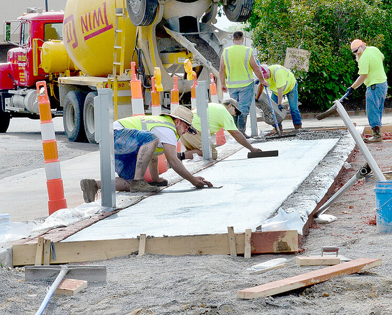 KEVIN HARVISON | Staff photo<br /> Workers finish the concrete for a sidewalk along Chickasaw Avenue Tuesday next to the Arvest water park.