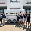 KEVIN HARVISON | Staff photo<br /> Shane Jones and the Patriot Chrysler Dodge, Jeep, Ram team, left, donated a 2020 14 foot tantum axle utility trailer with Signs By Jade custom Buffalo signage, to McAlester Buffalo Head Coach Forrest Mazey for the McAlester Buffalo football team to haul equipment to road games.