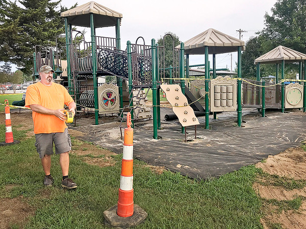 KEVIN HARVISON | Staff photo<br /> McAlester city employee Jeremy Lewis tapes off access to the new playground equipment at Conely Park. The playground should be open soon for play.