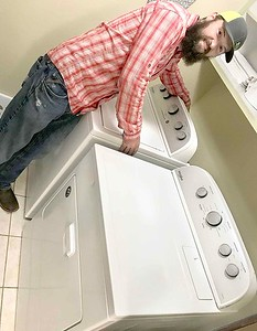 KEVIN HARVISON | Staff photo Joel Snow, President of UAW Local 1558 at Spirit Aero Systems looks over the washing machine the local donated to Youth Emergency Shelter Friday.