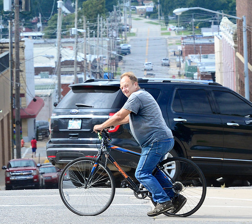 KEVIN HARVISON | Staff photo<br /> A bicyclist watches for traffic as he crosses Second Street on Washington Avenue.