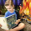 KEVIN HARVISON | Staff photo<br /> Chevylane Cooper reacts as he cozies up to an imaginary camp fire while he reads a book in Virginia Mayhew's class about a Berenstain Bears adventure.