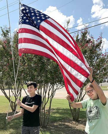 KEVIN HARVISON | Staff photo<br /> Pictured from left, Sixth Grade Students at Parker Middle School, Alyssa Grissom and Garrett Griffin, work together to bring down and in the flags flown over the school.