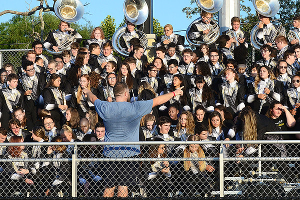 KEVIN HARVISON |<br /> McAlester Band Director Mark Price works to get the attention of the MHS students as the band groups together for a photo.