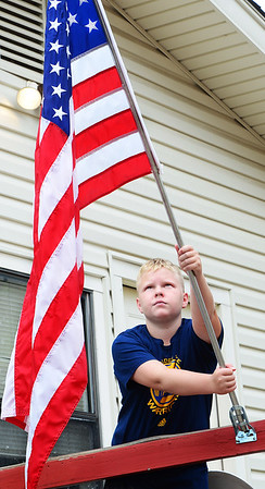 KEVIN HARVISON | Staff photo<br /> Landon Eddy puts out the American Flag at his McAlester home.