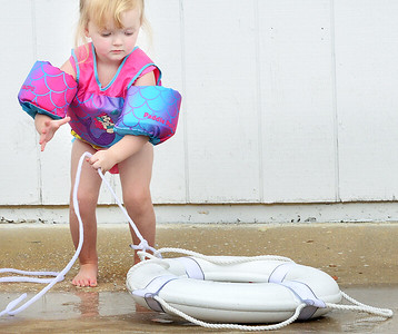 KEVIN HARVISON | Staff photo Two-year- old Jaxlynn Futral hauls in a life perserver at the Elks Lodge Swimming Pool during the Water Safety Course Tuesday.
