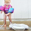 KEVIN HARVISON | Staff photo<br /> Two-year- old Jaxlynn Futral hauls in a life perserver at the Elks Lodge Swimming Pool during the Water Safety Course Tuesday.