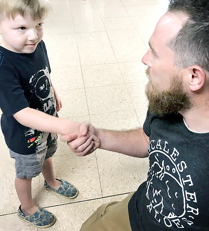 KEVIN HARVISON | Staff photo<br /> Isaac Giacomo, left introduces himself to new Jefferson Early Childhood Center Principal William Higgins, right, Thursday on the first day of school.
