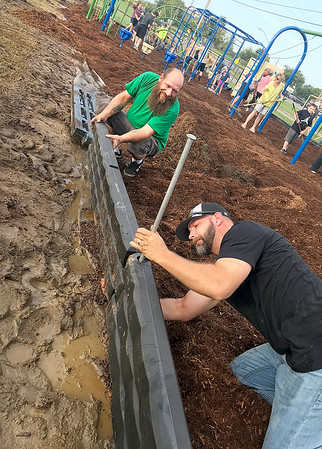 KEVIN HARVISON | Staff photo<br /> Kevin Walsh, green shirt, helps line up a barrier for KC Buck, black shirt as he secures a rod to hold it in place during a community volunteer day at Parker Middle School Saturday.