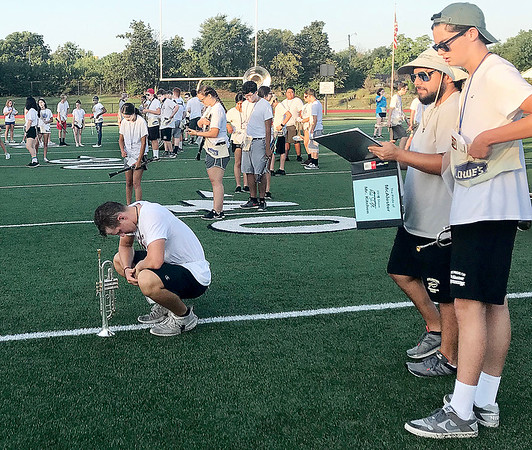 KEVIN HARVISON | Staff photo<br /> Second from the right, Bobby Kitchen goes over some formation movements with a MHS band member during a break as the band participates in a morning practice at Hook Eales Stadium.