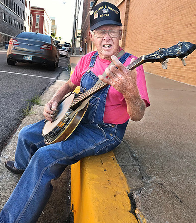 "KEVIN HARVISON | Staff photo<br /> Earl Lohr, from Kilgore Tx, plays his 1931 Gibson banjo as he sits on the curb while taking a break from walking downtown Choctaw Avenu ""killing time"" until it is time for his appointment. Lohr said he always keeps his banjo with him, so he always knows where it's at."