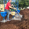 KEVIN HARVISON | Staff photo<br /> Mellisa Rock volunteers her time to help spread mulch around the new Park playground equipment Saturday.