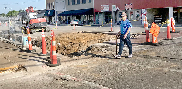 KEVIN HARVISON | <br /> A pedestrian makes his way across Choctaw Avenue Friday morning. Work continues for the improvements scheduled for downtown.
