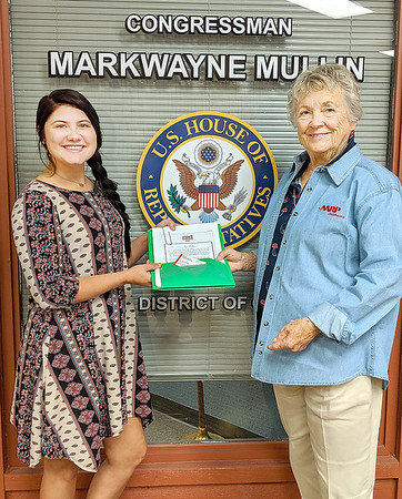 SUBMITTED PHOTO | <br /> Office aide Lacey Pitman in Congressman Markwayne Mullen's McAlester office accepts 2,271 petitions from District 2 residents. Oklahoma's Volunteer State AARP President (and McAlester resident) Joe Ann Vermillion delivered the petitions that ask the Congressman to vote protecting consumers from high pharmaceutical drug prices and to protect Social Security as well as Medicare.