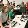 KEVIN HARVISON | Staff photo<br /> Adults and 4H students gather Wednesday moring at the Southeast Expo Building to prepare for the upcoming Pittsburg County Free Fair.
