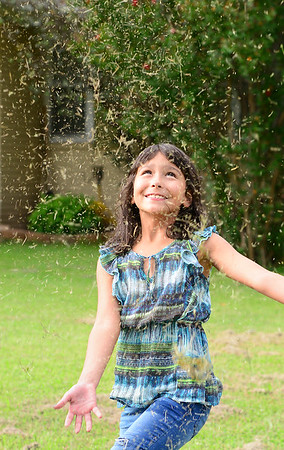 KEVIN HARVISON | Staff photo<br /> Emily Bryson throws dry grass in the air to create her own version of a snowy day.
