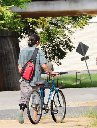 KEVIN HARVISON | Staff photo<br /> A bicyclist watches prepares to cross Main Street on Cherokee Avenue.