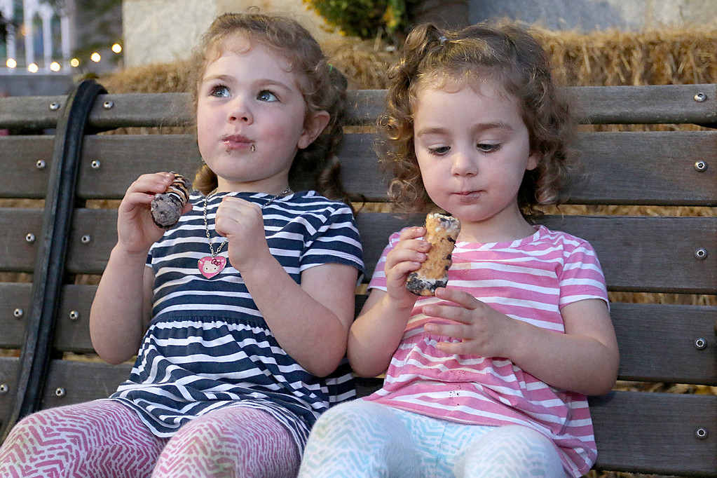 . Enjoying some Oreo-flavored cannoli is sisters Paige, 4, and Quinn Dickhaut, 2, from Fitchburg at the Leominster Cannoli Festival on Thursday night. SENTINEL & ENTERPRISE/JOHN LOVE