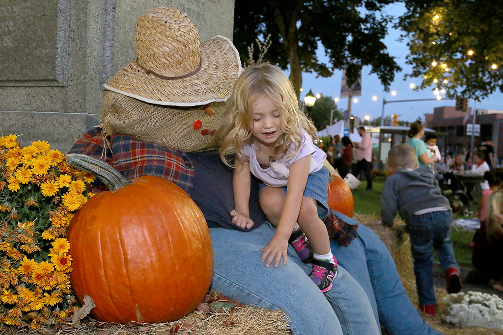 . Enjoying the scarecrows on Monument Square in Leominster during the Cannoli Festival is Ava Soares, 2, from Marlboro. SENTINEL & ENTERPRISE/JOHN LOVE
