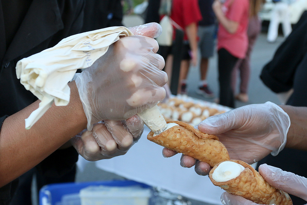 . Leominster CTei culinary students Chris Agosto, 17 on right, and Moses Perez, 17, fill cannoli cones during the Leominster\'s Cannoli Festival on Thursday night. SENTINEL & ENTERPRISE/JOHN LOVE