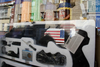 Same flag reflected in the window of a store selling a BB gun and BBs.