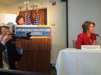 Rep. Pelosi interacting with an off-camera audience member. At the podium is the head of St. Mary's hospital.
