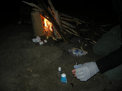 David has the campfire roaring while Ben experiments (see the cotton balls with various fuels?)